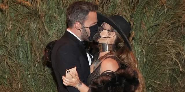 Ben Affleck and Jennifer Lopez are seen sharing a kiss through their masks at the Met Gala.