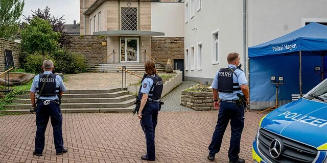 Police officers stay in front of the entrance to the Jewish Community building in Hagen, Germany, Tursday, Sept. 16, 2021.