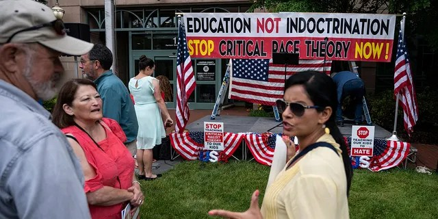 """People talk before the start of a rally against """"critical race theory"""" (CRT) being taught in schools at the Loudoun County Government center in Leesburg, Virginia on June 12, 2021. (Photo by ANDREW CABALLERO-REYNOLDS / AFP) (Photo by ANDREW CABALLERO-REYNOLDS/AFP via Getty Images)"""