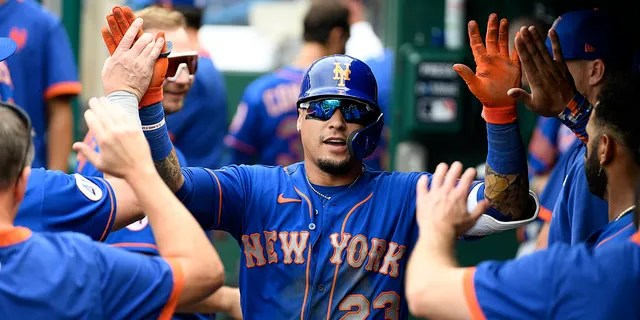 The New York Mets' Javier Baez celebrates his home run in the dugout during the third inning of a baseball game against the Washington Nationals, Sunday, Sept. 5, 2021, in Washington. (AP Photo/Nick Wass)