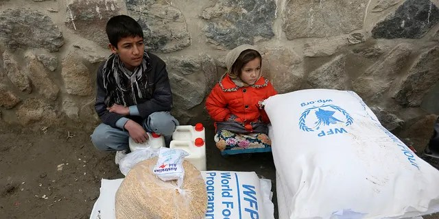 In this Jan. 24, 2017 file photo, children wait for transportation after receiving food donated by the World Food Program, in Kabul, Afghanistan. On Friday, Oct. 9, 2020 the WFP won the 2020 Nobel Peace Prize for its efforts to combat hunger and food insecurity around the globe.