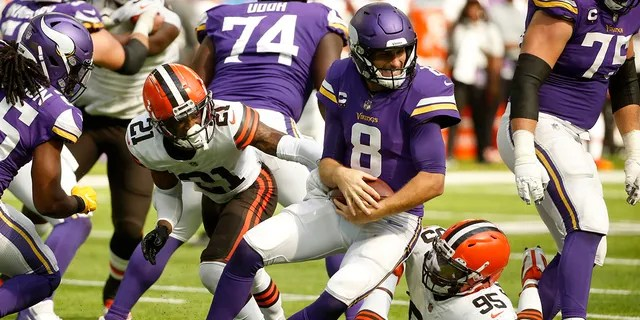 Minnesota Vikings quarterback Kirk Cousins (8) is sacked by Cleveland Browns cornerback Denzel Ward (21) and defensive end Myles Garrett (95) during the second half of an NFL football game, Sunday, Oct. 3, 2021, in Minneapolis.