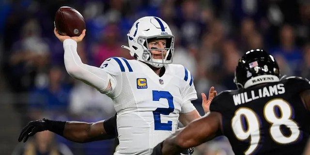 Indianapolis Colts quarterback Carson Wentz (2) throws the ball under pressure from Baltimore Ravens nose tackle Brandon Williams (98) during the first half of an NFL football game, Monday, Oct. 11, 2021, in Baltimore.