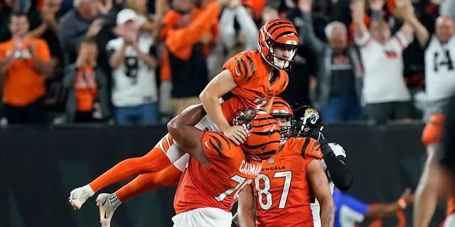 Cincinnati Bengals kicker Evan McPherson (2) celebrates with Jackson Carman (79) after kicking the game-winning field goal against the Jacksonville Jaguars in an NFL football game, Thursday, Sept. 30, 2021, in Cincinnati. Cincinnati won 24-21.