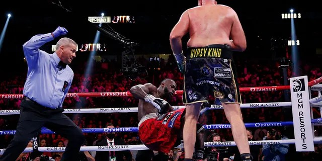 Tyson Fury, of England, knocks down Deontay Wilder in a heavyweight championship boxing match Saturday, Oct. 9, 2021, in Las Vegas.