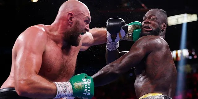 Tyson Fury, of England, lands a left to Deontay Wilder in a heavyweight championship boxing match Saturday, Oct. 9, 2021, in Las Vegas.