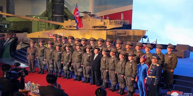 North Korean leader Kim Jong Un, center, poses for a group photo with fighter pilots who made the demonstration flight at the opening of an exhibition of weapons systems in Pyongyang, North Korea, on Monday. (Korean Central News Agency/Korea News Service via AP)