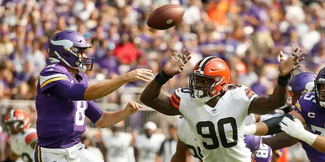 Cleveland Browns defensive end Jadeveon Clowney (90) pressures Minnesota Vikings quarterback Kirk Cousins (8) as he throws a pass during the first half of an NFL football game, Sunday, Oct. 3, 2021, in Minneapolis.