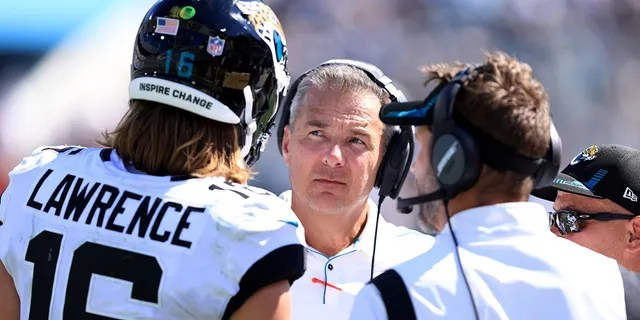 Head coach Urban Meyer of the Jacksonville Jaguars speaks with Trevor Lawrence #16 during the game against the Arizona Cardinals at TIAA Bank Field on September 26, 2021 in Jacksonville, Florida.