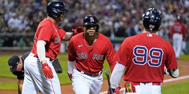 Boston Red Sox's Xander Bogaerts, middle, celebrates his two-run homer with Rafael Devers, left, and Alex Verdugo (99) in the first inning of the American League Wild Card playoff baseball game against the New York Yankees at Fenway Park, Tuesday Oct. 5, 2021, in Boston.