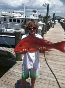 Alabama Gulf Coast semi-private snapper fishing charter curly hair boy with his catch
