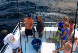 AL Gulf Coast deckhand assisting anglers during a gulf shores al trolling fishing charter
