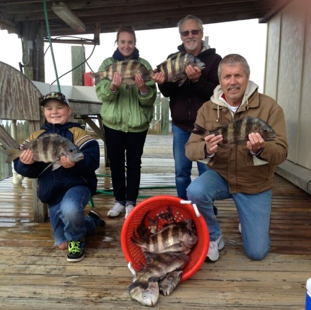 Family of IL anglers enjoying winter inshore fishing sheepshead at dock