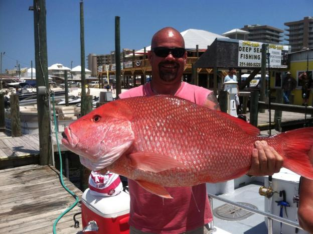 Angler showing 21 lb. Red Snapper at Florabama Marina caught on the F/V Sure Shot