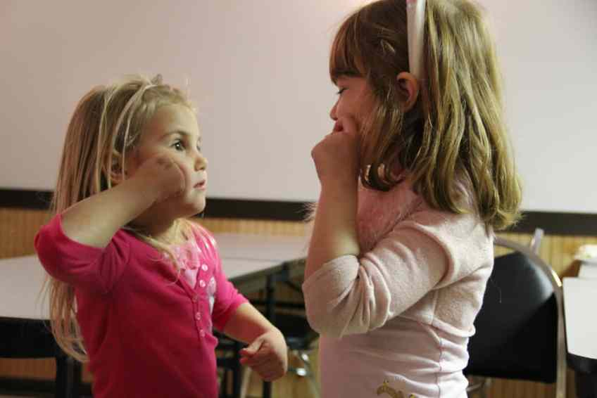 two young girls using sign language