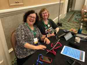 Image of Kathryn and Kim sitting at a table with an iPad mounted on an industrial twist tie.