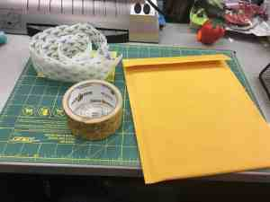 Image of a padded mailer, duct tape, and velcro sitting on a counter.