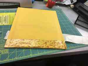 Image of a padded mailer being covered in duct tape.
