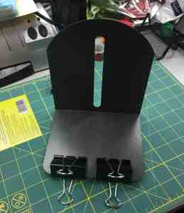 Image of a bookend with binder clips attached at the bottom