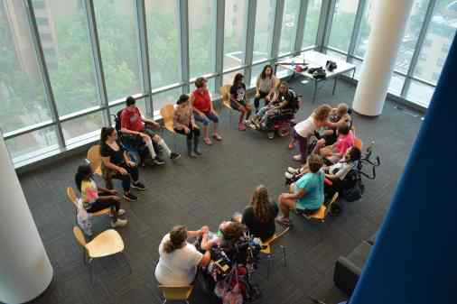 Image of a circle formed by ACES participants doing yoga in a glass-walled room