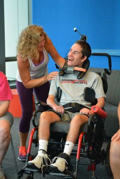 YOung man in wheelchair smiling at yoga instructor