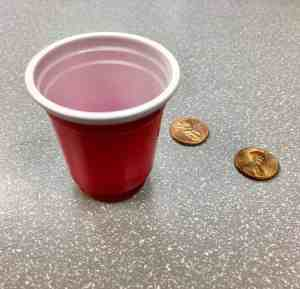 Image of a mini red solo cup with pennies
