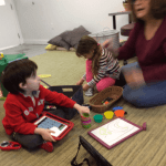 child using an AAC device in play