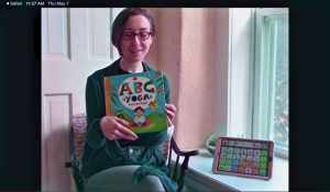 Woman reading ABCs Yoga and modeling in AAC device.