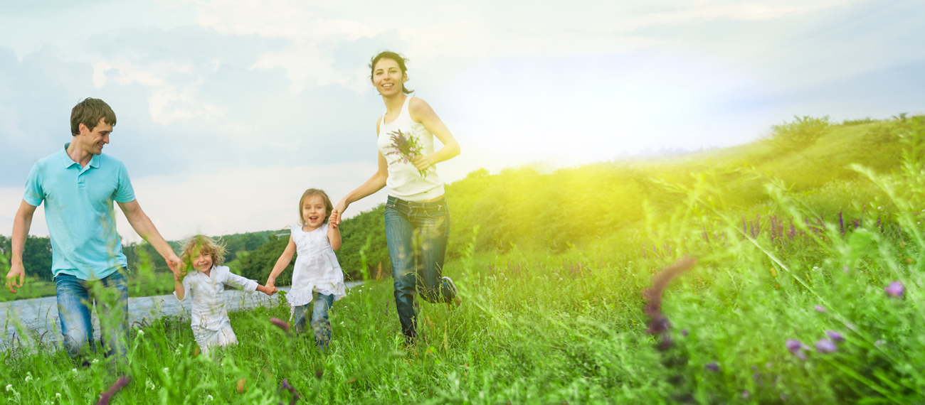 Young family running through a field