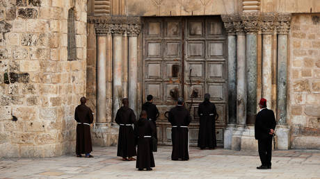 Monks pray in front of the locked door of Jerusalem's Church of the Holy Sepulchre. © REUTERS/ Ammar Awad