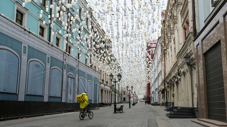 A Yandex.Eats food delivery courier rides a bicycle along a street past closed shops in Moscow