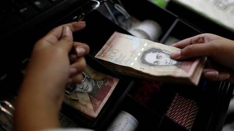 FILE PHOTO: A cashier counts Venezuelan bolivar notes © Reuters / Ueslei Marcelino