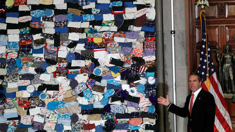 Andrew Cuomo next to mural made up of hundreds of face masks in New York