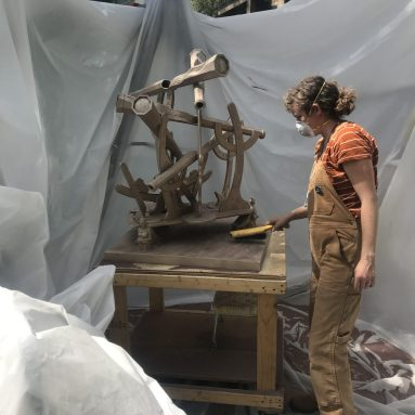 Lauren in process of sandblasting the sextant sculpture