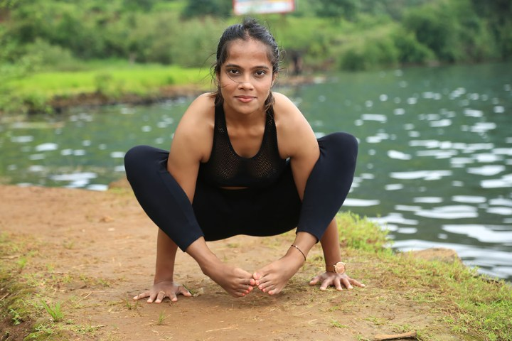 a girl performing the Insect pose in yoga
