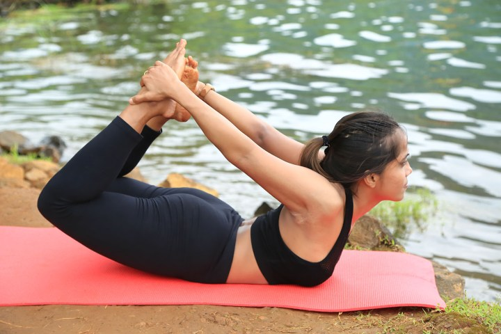 A girl doing bow pose as a part of her yoga routine