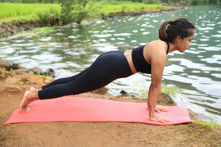 a girl performing the Plank pose in yoga as part of an ab routine