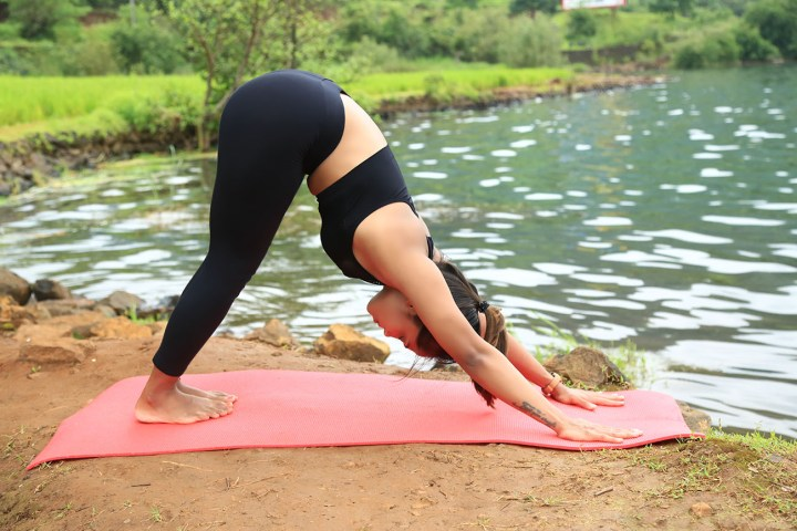 A girl doing Downward Dog Pose to cure arthritis pain