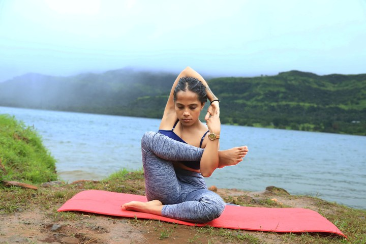 a girl performing the baby cradle pose to open hips for the elephant trunk pose in yoga