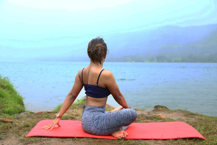 a girl performing the Seated Twist pose in yoga for a healthy spine