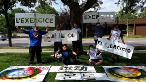 "Stencil Art picture participants in North Minneapolis, with signs saying ""exercise"" in various languages. (Asian Media Access photo)"