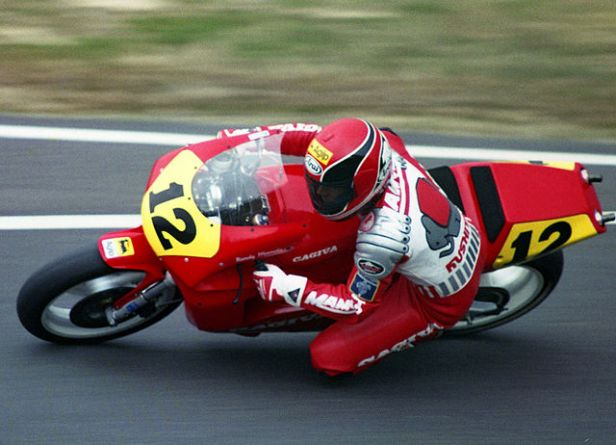 Color photo of motorcycle rider with knee down on Cagiva GP motorcycle