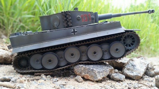 Color photograph of dark grey model Tiger tank going over some stones