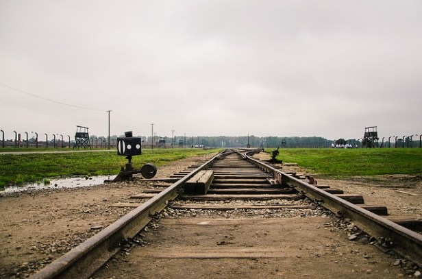 Holocaust short stories image: Color photograph of railway line leading to extermination camp,which is in the distance.