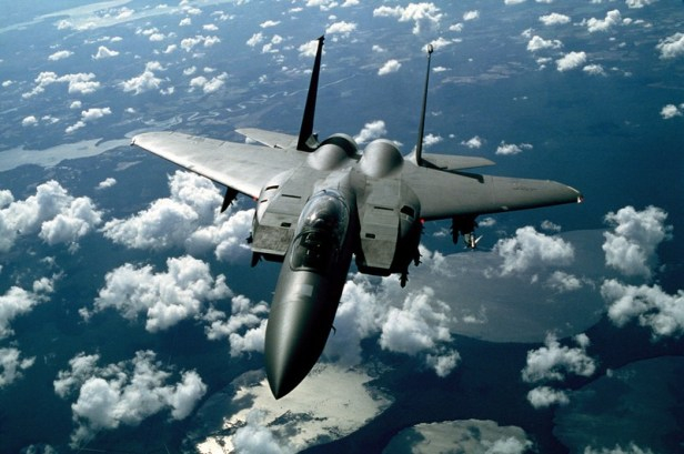 Colored photograph of dark gray  jet fighter F-15 strike eagle ,as appears in Aaron David Yeoman's political thriller novels,flying above the clouds