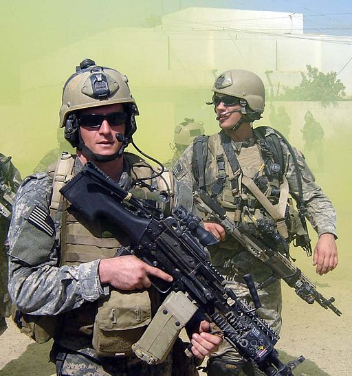 Colour photograph of two U.S. Navy SEALs in combat uniform carrying combat weapons.