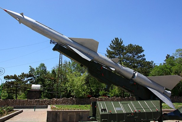 Color photograph of Soviet surface to air missile on display with garden in background. Prequel to Eleventh Hour Covenant