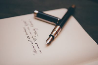 Colored photograph of sheet of paper with some writing on it and an open fountain pen with its lid beside it. Short fiction stories about the Holocaust.