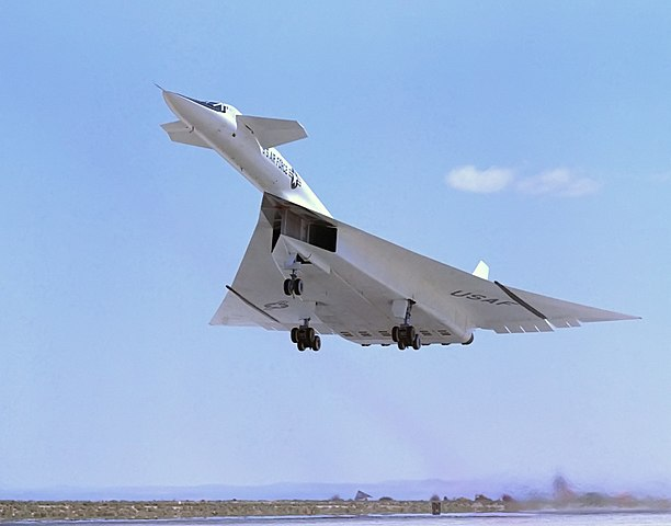 Colored photograph of an aircraft lifting off from the runway. Photo shows the underside of the mostly white plane. Blue sky with just a strip of horizon.Linda Evangelista.