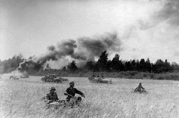 Black and white photograph of soldiers in armored vehicles in a field. A row of tall trees and a lot of smoke billowing in background. Sven or Sajer.